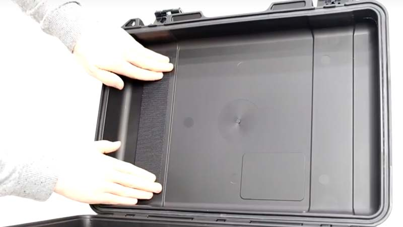 Hands fitting a Velcro strip to the lid of a Peli Storm case